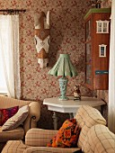 Beige armchairs, table lamp with fabric lampshade on white-painted wooden table in corner below painted wooden horse head on wall