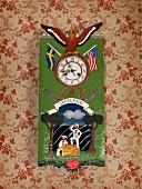 Wanduhr mit bemaltem Blech, Fahnen und Adlermotive, aufgehängt an tapezierter Wand mit nostalgischem, floralem Muster