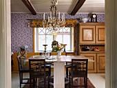 Blick ins Esszimmer auf rustikalen Tisch weiss lackiert und dunkle Holzstühle, im Hintergrund Anrichte mit geschnitzten Paneelen neben Fenster