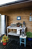 Anrichte aus Holz auf Terrasse vor Hauswand mit Holzverschalung