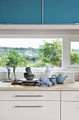 Detail of kitchen counter; wooden worksurface on white base units below window and blue wall-mounted units