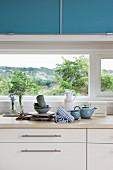 Ausschnitt einer Küchenzeile, Holz Arbeitsplatte auf weißem Unterschrank vor Fenster, oberhalb Hängeschrank in Blau