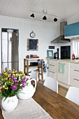 White vase of flowers on wooden table in front of kitchen counter against wood-clad white wall