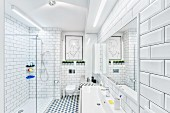 White, modern bathroom with tiled walls & floor, strip lights over washstand & glazed, floor-level shower; modern artwork above wall-mounted toilet