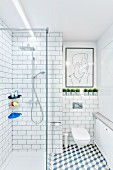 White, modern bathroom with tiled walls & floor, glazed, floor-level shower and modern artwork above wall-mounted toilet