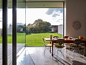 Classic wire-framed chairs around wooden dining table with place settings in front of glass wall with garden view