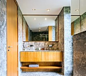 Designer bathroom with pale grey, marble-tiled walls and floor and fitted washstand with wooden base unit on mirrored wall