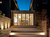 Steps leading to contemporary extension between two houses at night with view into illuminates dining room