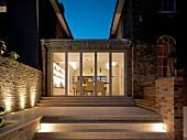 Eingeschossiger Anbau mit Treppenanlage zwischen zwei Wohnhäusern, bei Nacht, beleuchtetes Esszimmer