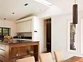 View across dining area into open-plan kitchen with solid wood counter and white wall units