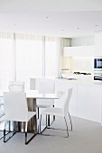 Dining table and open-plan kitchen area in white, elegant interior