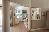 Doorway leading into kitchen flanked by columns; white fitted kitchen with mosaic splashback, retro cooker, retro fridge and breakfast bar