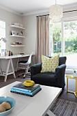 Wohnraum mit Sitzbereich aus Sessel & Sofatisch sowie Arbeitsbereich mit Schreibtisch, Bürostuhl & Regal in Zimmerecke am Fenster
