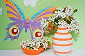 White lavender in a retro ceramic vase with orange and white strips and an orange bowl against a wall painted with a colourful butterfly