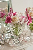Pink and white roses with jasmine flowers in a glass