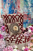 An upholstered chair with a burn-out pattern and a cushion in a sea of hydrangeas, roses and dahlias