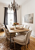 Chairs with beige upholstery at rustic dining table below chandelier in corner of traditional living room