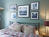 Black metal double bed with checked bed linen below framed black and white photos on pastel green wall