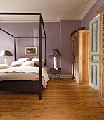 Modern wooden double bed with canopy frame in bedroom with mauve walls and rustic wooden floor