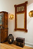 Stacked antique trunks, candle lantern on floor and mirror with carved gilt frame flanked by brass candle sconces