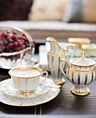 Traditional white coffee cup, sugar bowl and milk jug with gilt pattern