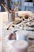 Various paintbrushes in metal holder on artist's studio table