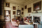 Oil portraits and antique furniture in living room of English manor house