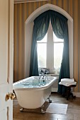 Free-standing bathtub in front of window with Tudor arch and draped petrol-blue curtains combined with multicoloured striped wallpaper