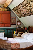 Antique sleigh bed under sloping bedroom ceiling with floral wall hanging