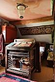 Vintage Stehpult aus Holz vor Bett, an Dachschräge floral gemusterter Wandbehang im Schlafzimmer