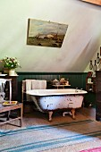 Free-standing vintage bathtub against green-painted wainscoting on sisal rug in bathroom with sloping ceiling