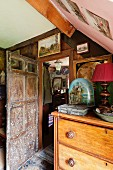 Antique objects on top of chest of drawers next to open wooden door