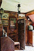 Antique pictures and old hurricane lamp in wood-panelled interior