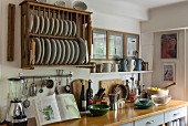 White crockery in wooden plate rack above counter in rustic kitchen
