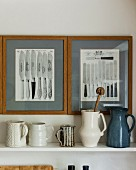 Collection of jugs on shelf below framed pictures of knives on wall