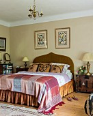 Elegant double bed with curved headboard and silk bed linen in traditional bedroom