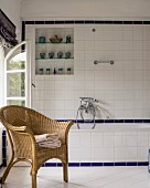 Wicker chair next to bathtub in tiled bathroom