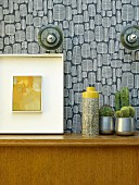 Vase next to cacti and picture on wooden cabinet against wall with retro wallpaper