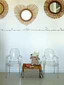 Wicker trunk between Ghost chairs below round mirrors with sunburst frames