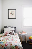 Soft toys and hand-made quilt on child's bed next to stool
