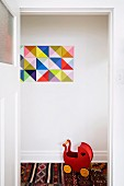 Red wooden retro dolls' pram on ethnic rug below geometric picture on wall