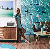 Woman on sideboard in retro living room with brown leather sofa and classic lamp in front of wallpaper with leaf motif