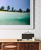 Sideboard with retro utensils against a white brick wall and a framed color photo