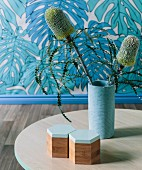 Exotic flowering plant in light blue base on table, wallpaper with leaf motif behind it