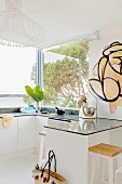Modern, white kitchen with stone worktop in front of a window with a view