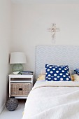 Bed with upholstered headboard and blue and white polka dot pillow, simple bedside table with drawer and cross on the wall