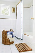 Rustic laundry basket with blue and white striped towels on tiled floor in front of bathtub with white shower curtain