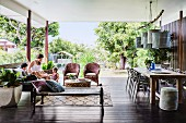 Light furnishings and pendant lamps above dining table on roofed terrace with garden in background
