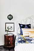 Cushions and throw on bed with ornate headboard next to spherical glass lamp above round bedside cabinet
