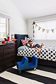 Boy lying on bed with black and white polka-dot bedspread below bunting and next to chest of drawers in child's bedroom